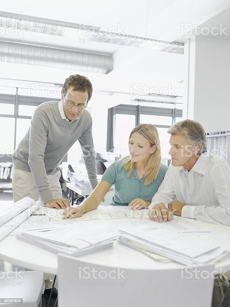 Couple reviewing blueprints with architect royalty-free stock photo
