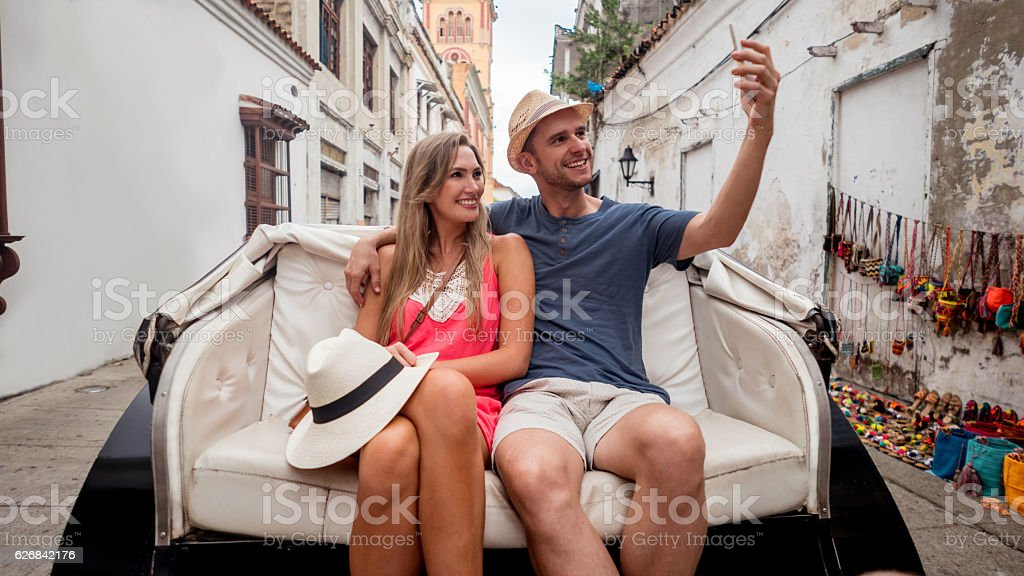 Couple riding a carriage and taking a selfie stock photo