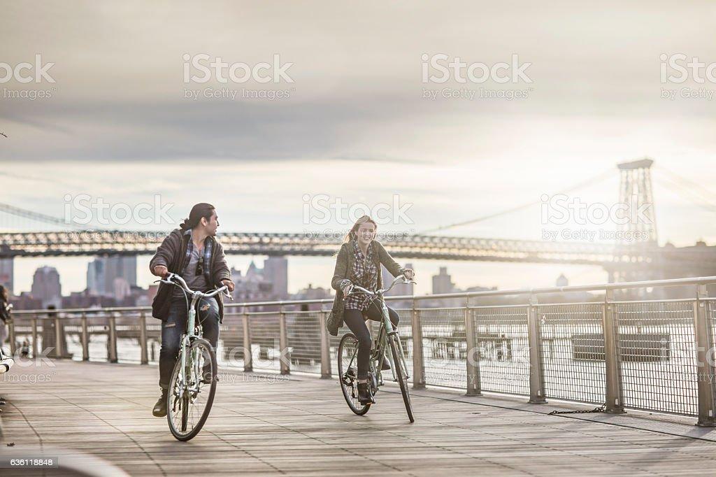 Couple riding bicycles against Williamsburg Bridge stock photo