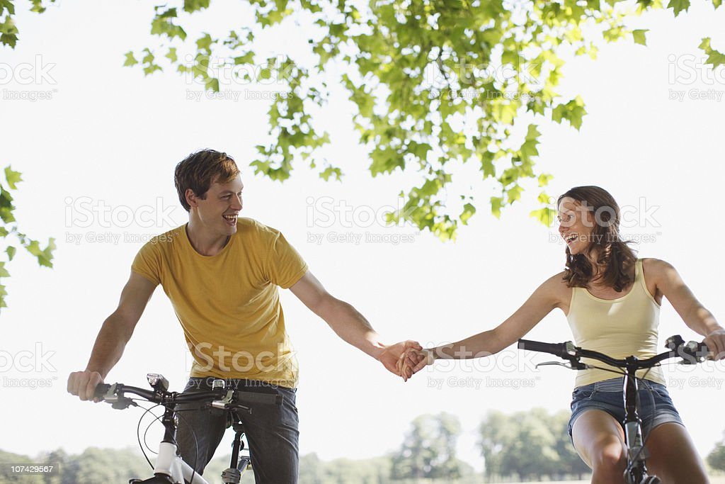 Couple riding bicycles and holding hands royalty-free stock photo