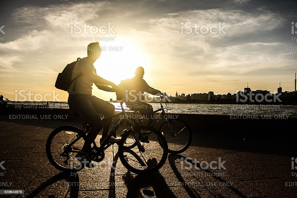 Couple Riding Bicycles at Sunset in Montevideo stock photo