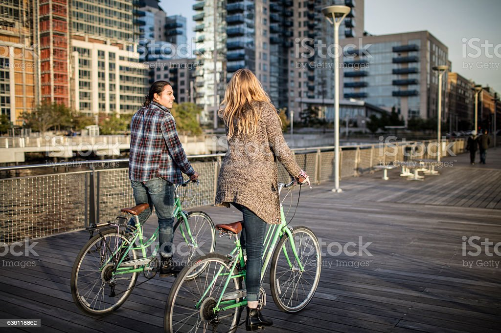 Couple riding bicycles on boardwalk in city stock photo