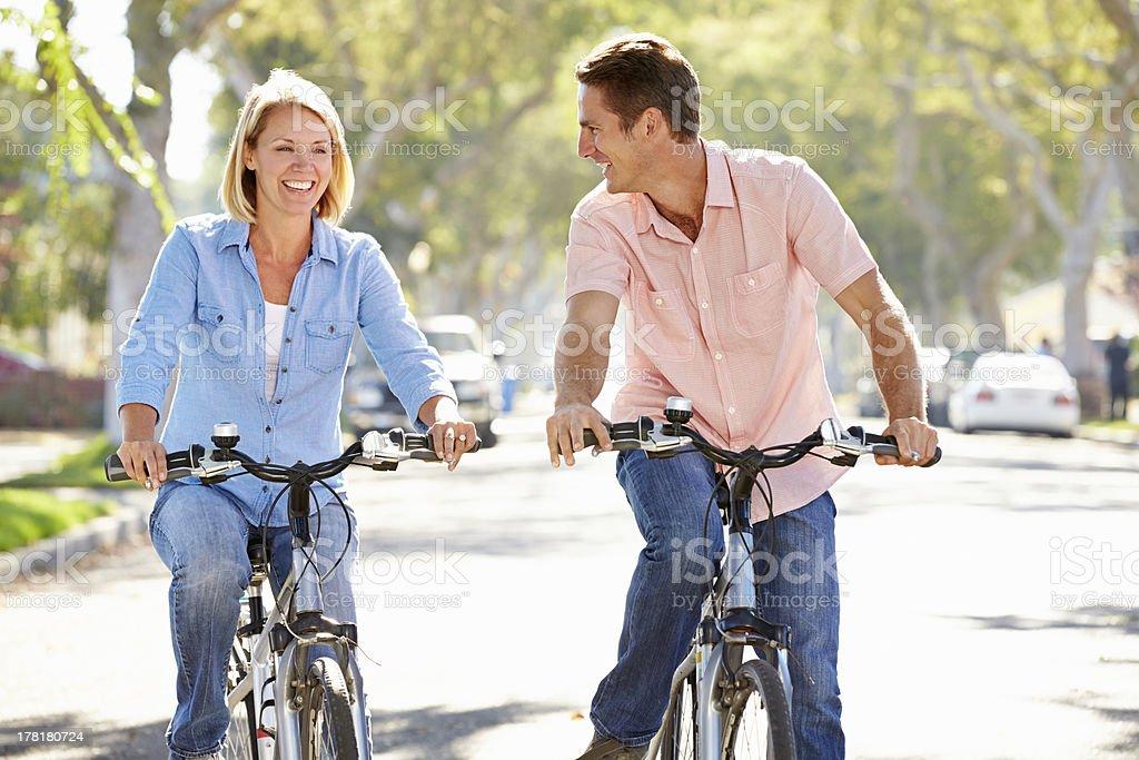 Couple riding bicycles on suburban street stock photo