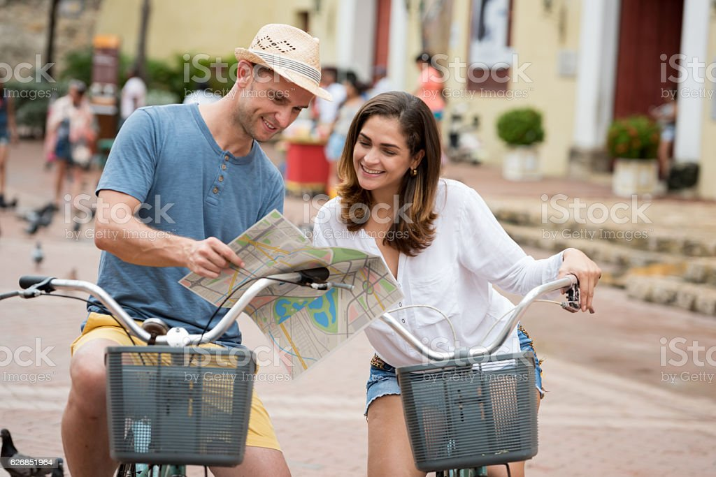 Couple riding bikes and looking at a map stock photo
