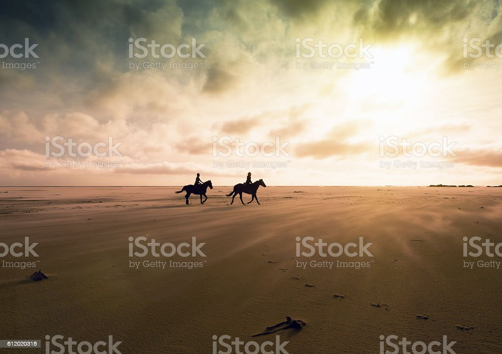 Couple riding horses across deserted sands at sunset stock photo