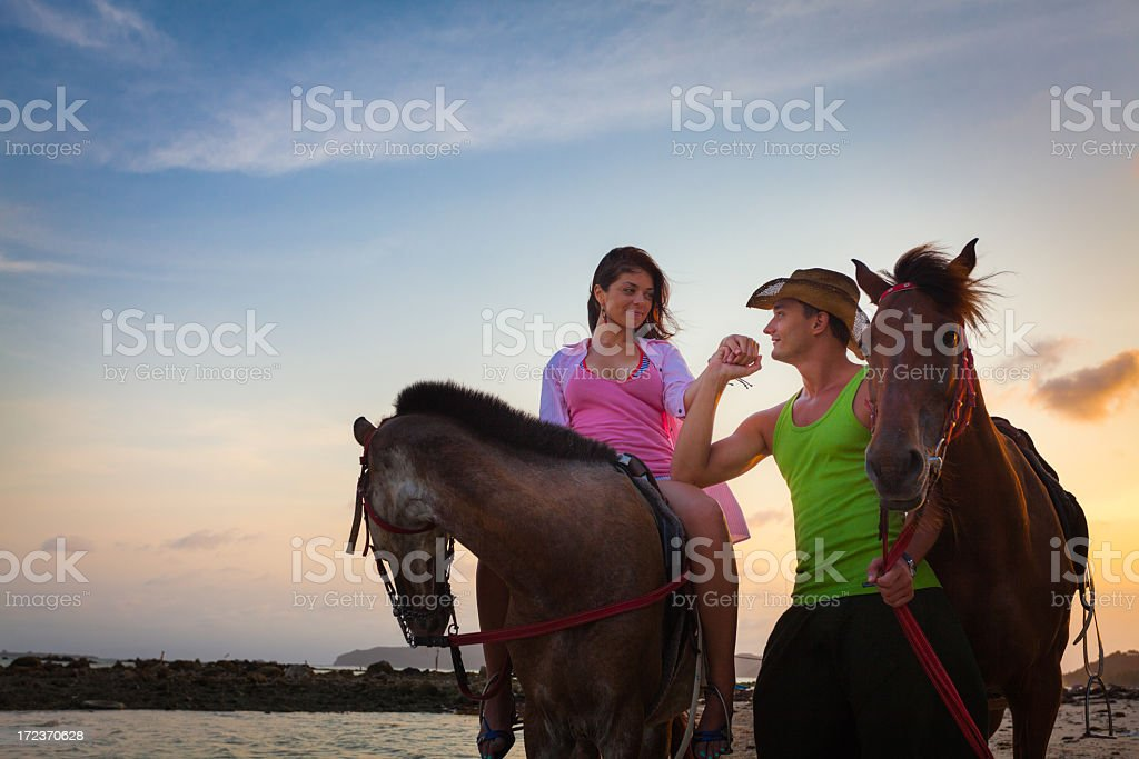 Couple riding horses at sunset royalty-free stock photo