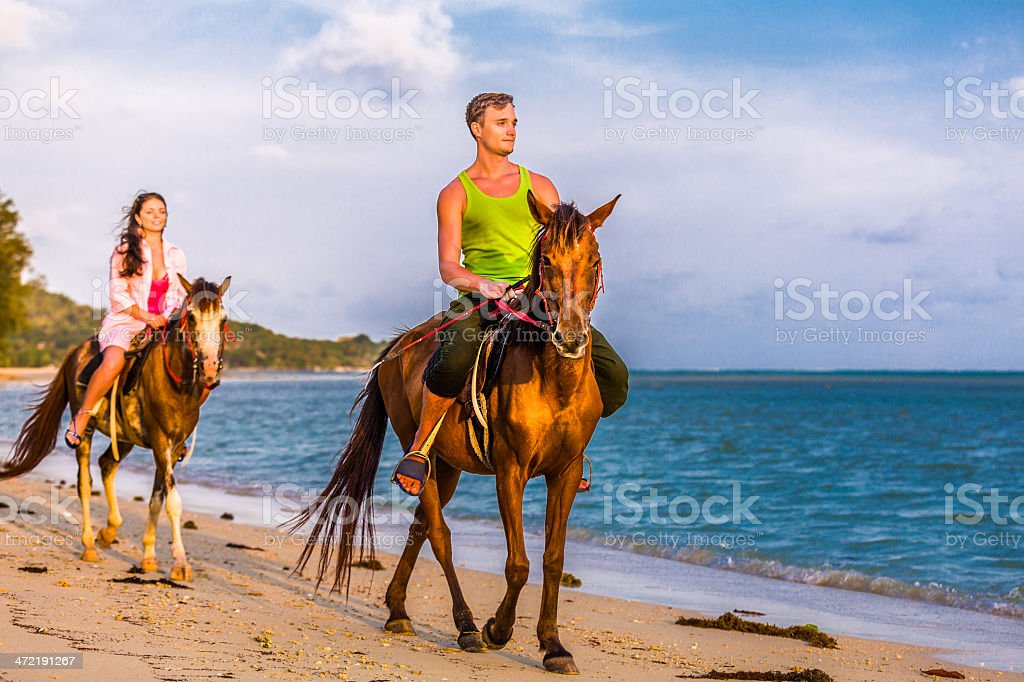 Couple riding horses at sunset stock photo
