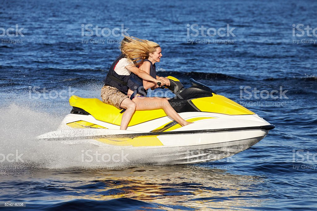 Couple riding jet ski stock photo