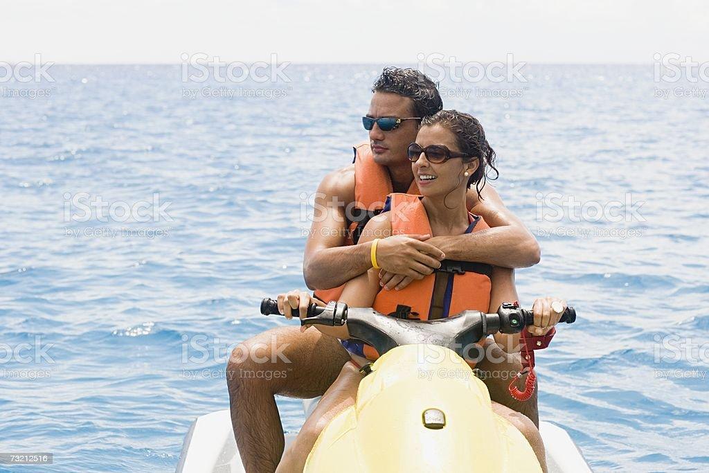 Couple riding jet ski stock photo