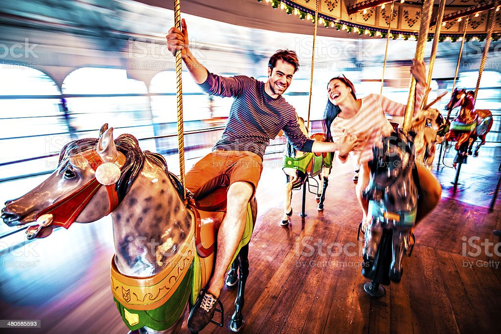 Couple riding merry-go-round in LA stock photo