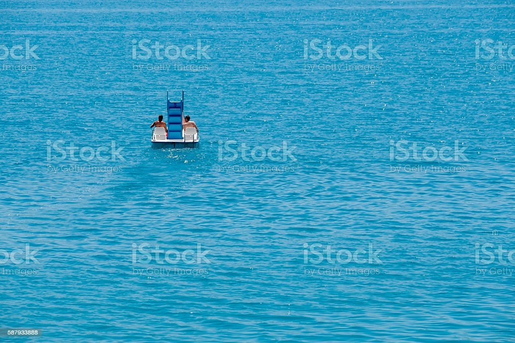 Couple riding pedal boat stock photo