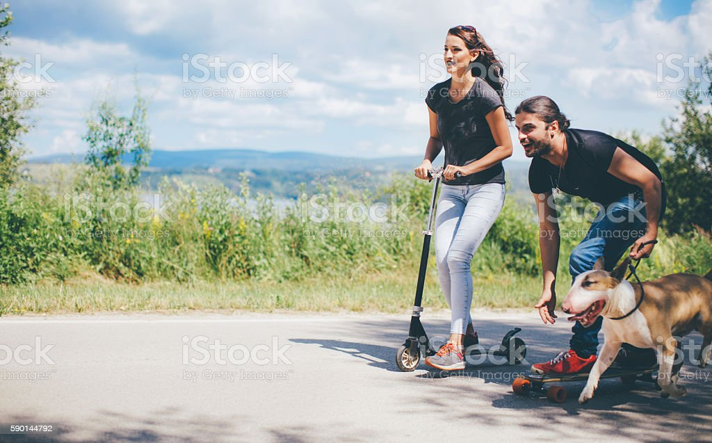 Couple riding scooter with their dog stock photo