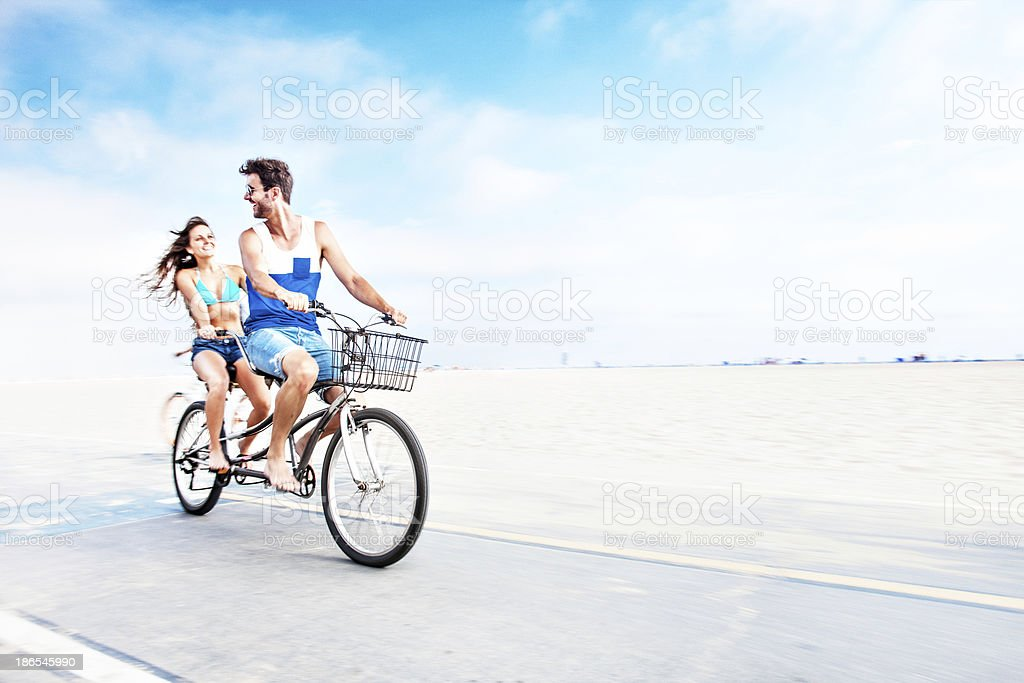 Couple riding tandem bicycle royalty-free stock photo
