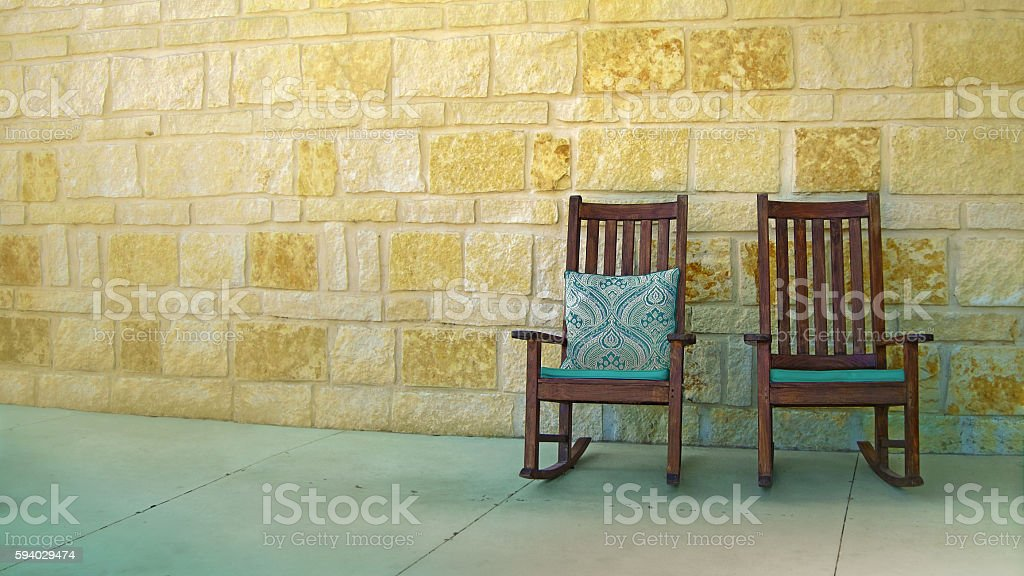 couple rocking chairs by stone wall stock photo