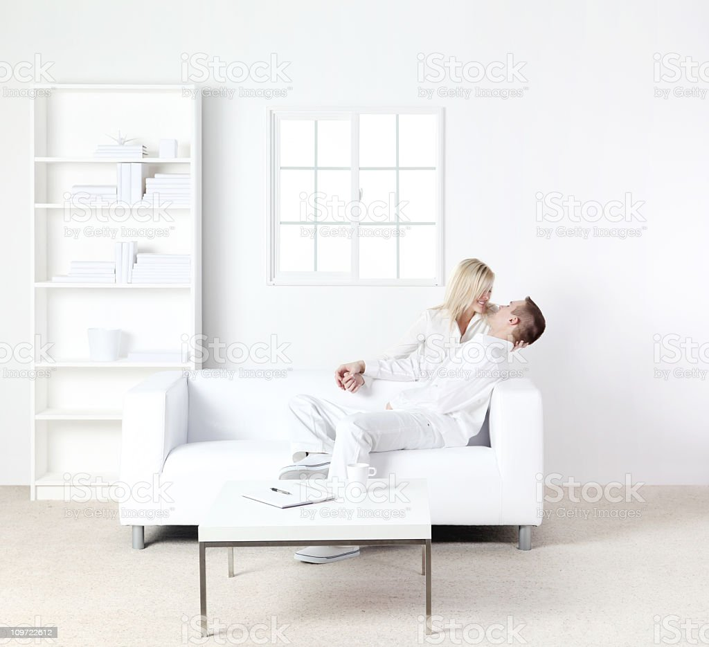 Couple romancing on a couch royalty-free stock photo