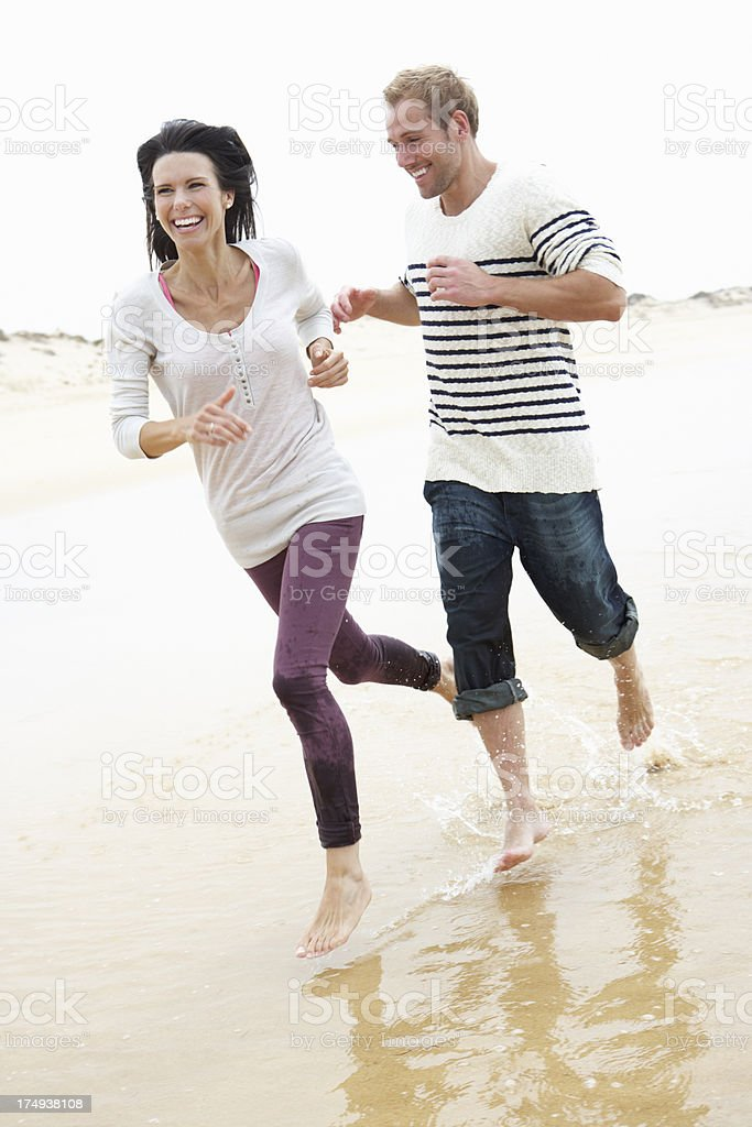 Couple Running Along Beach Together royalty-free stock photo