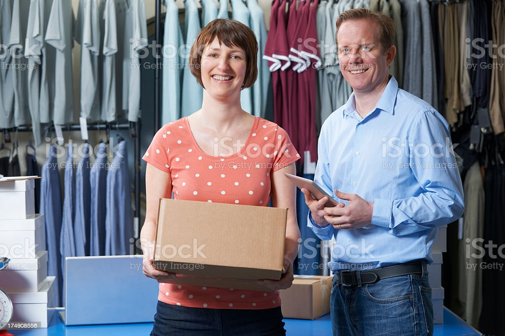 Couple running an online clothing business carrying a box royalty-free stock photo