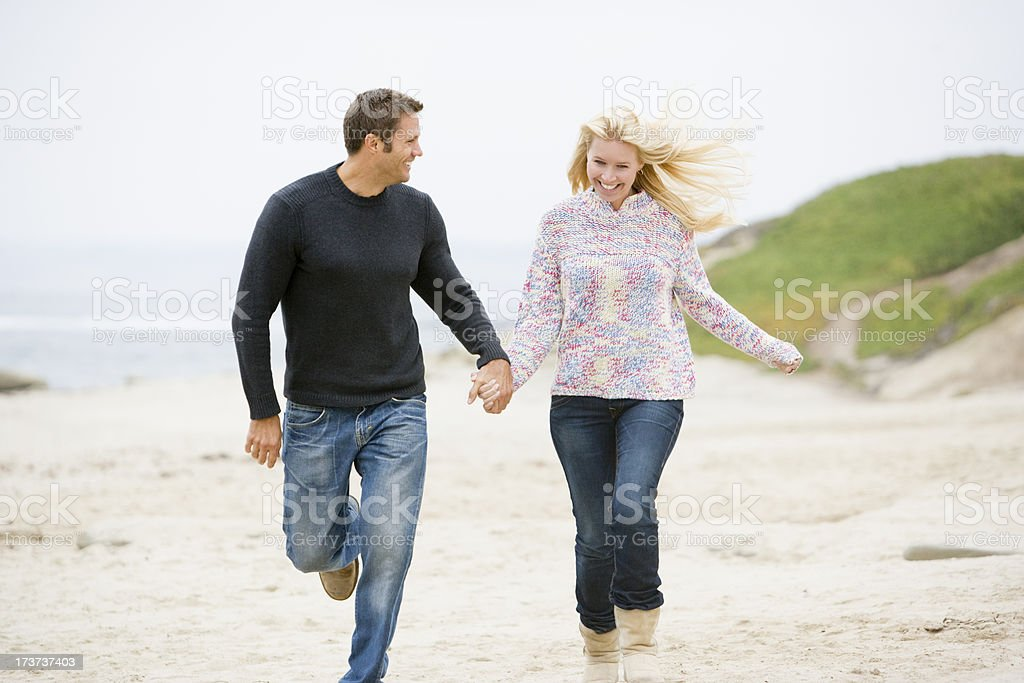 Couple running at beach holding hands smiling royalty-free stock photo