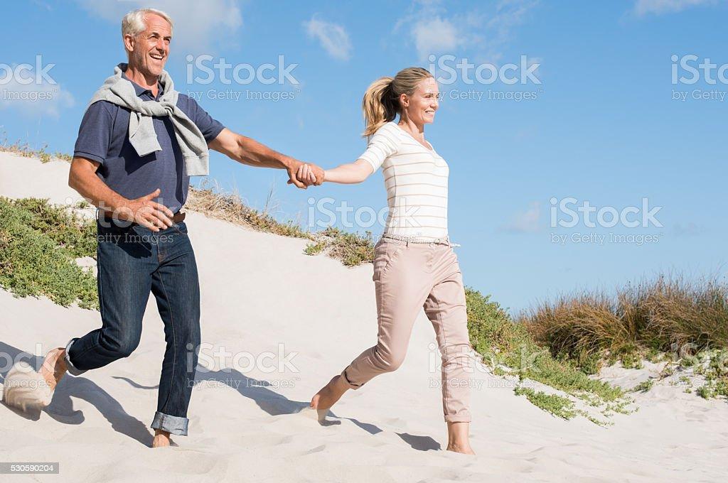 Couple running down dune stock photo