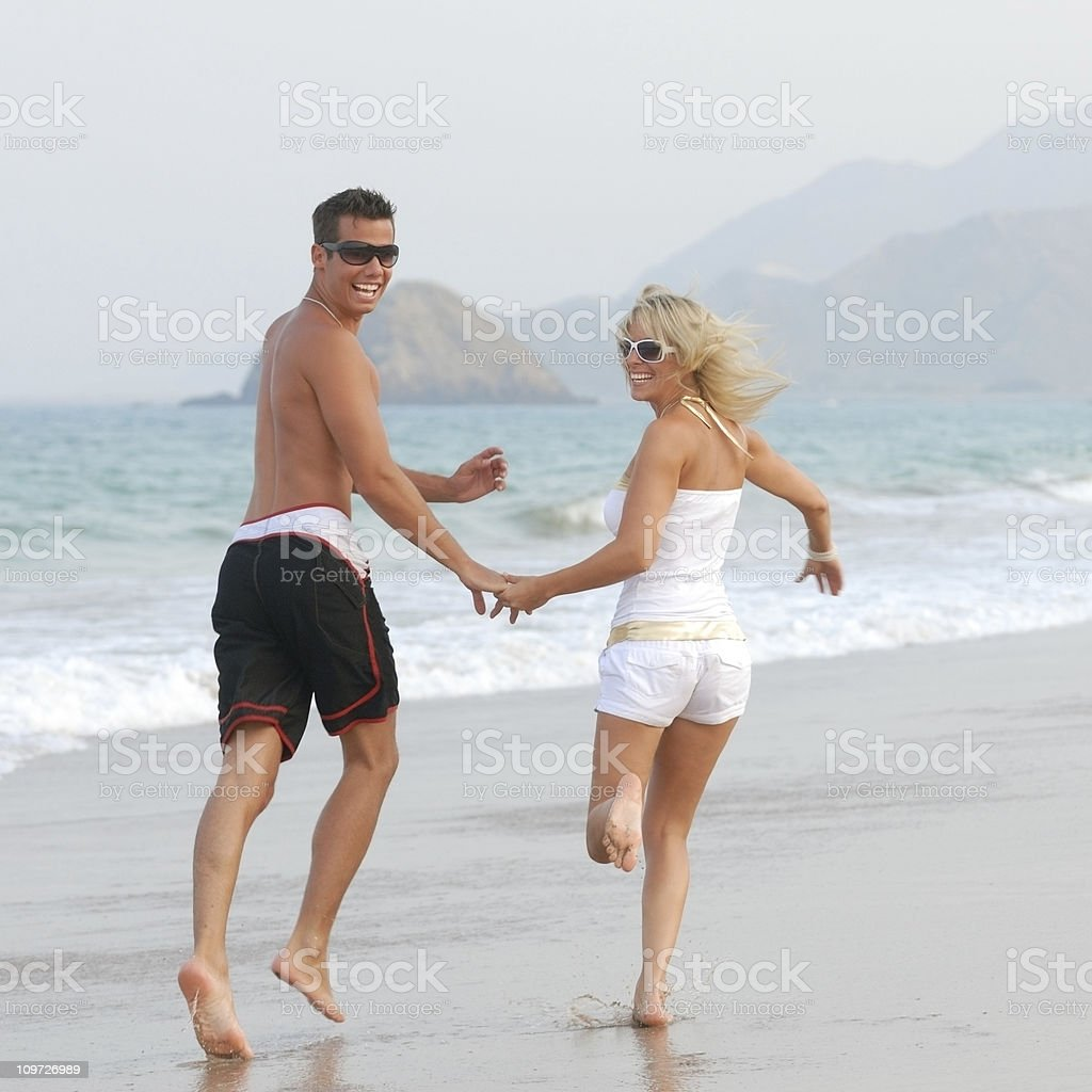 Couple running down the beach royalty-free stock photo