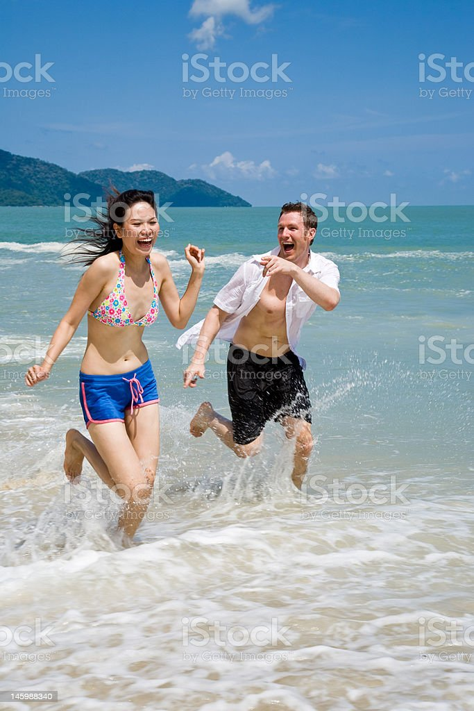 couple running frantically on the beach with joy royalty-free stock photo