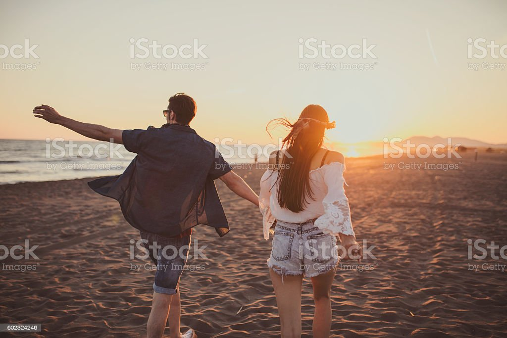 Couple running free on the beach while holding hands stock photo