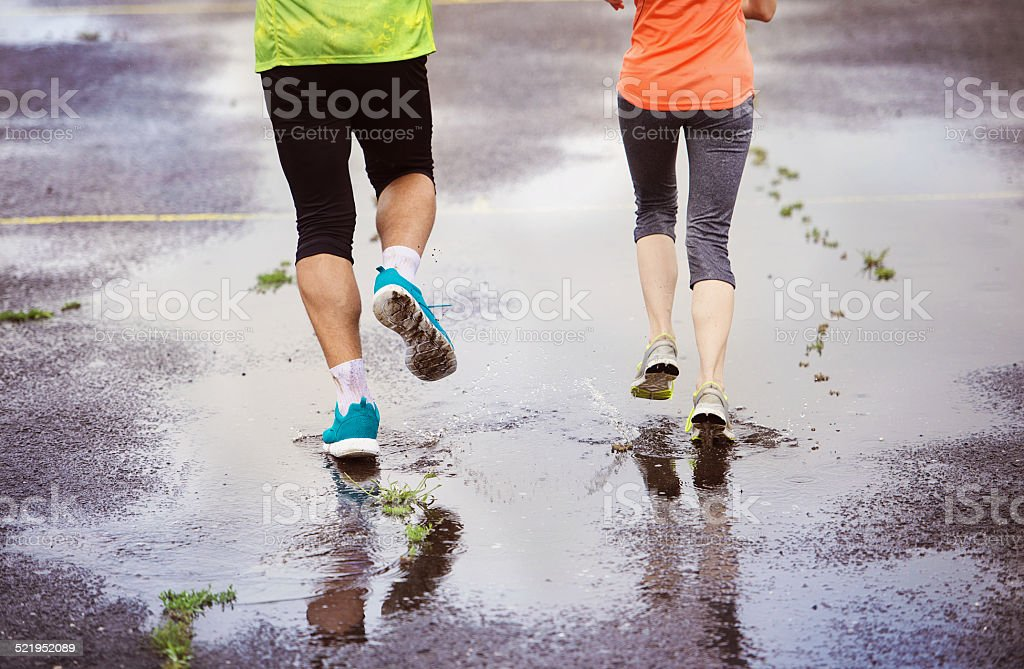 Couple running in rainy weather stock photo