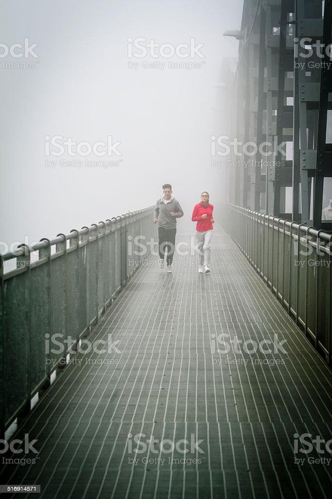 Couple Running in the fog on Iron Bridge stock photo