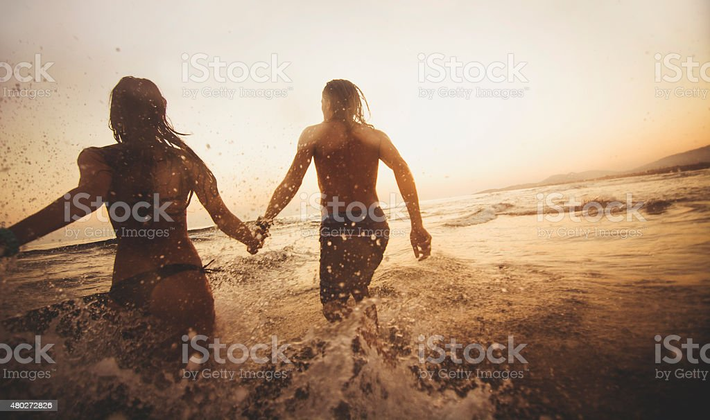 Couple running in the water stock photo