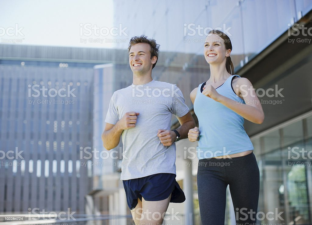 Couple running in urban setting royalty-free stock photo