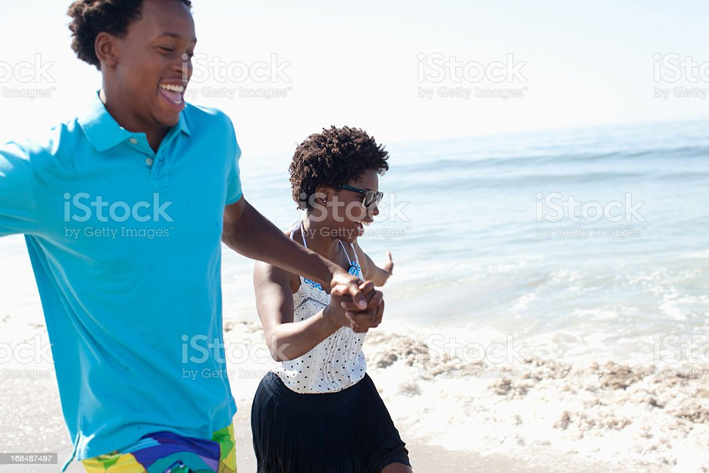 Couple running in waves on beach stock photo