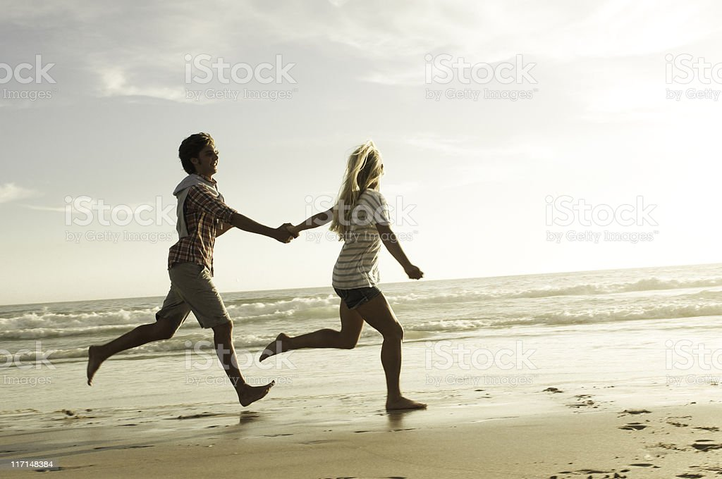 Couple running on beach stock photo