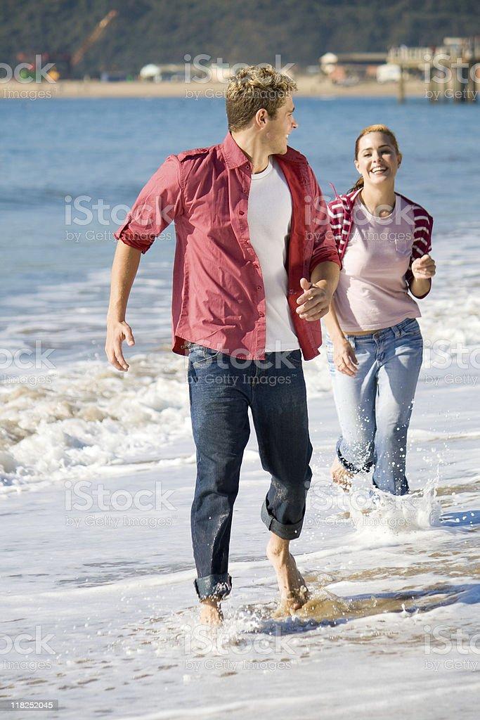 couple running on beach royalty-free stock photo