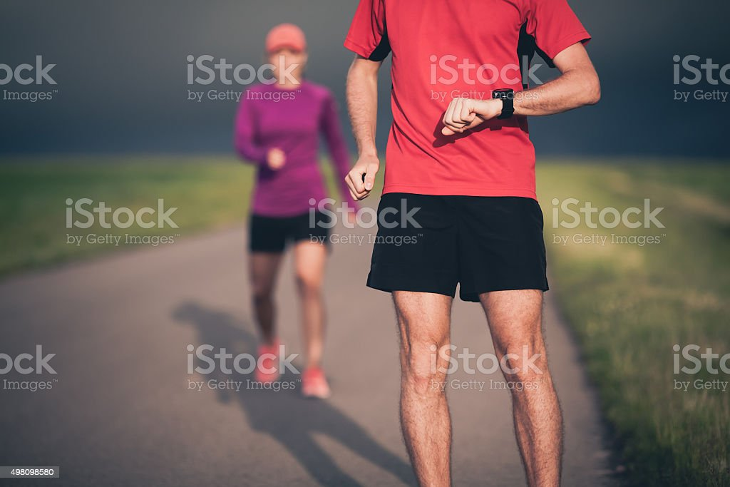 Couple running on country road stock photo