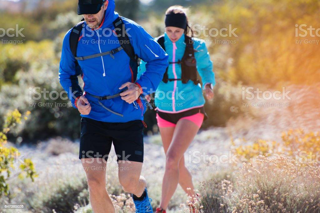 Couple running on mountain stock photo