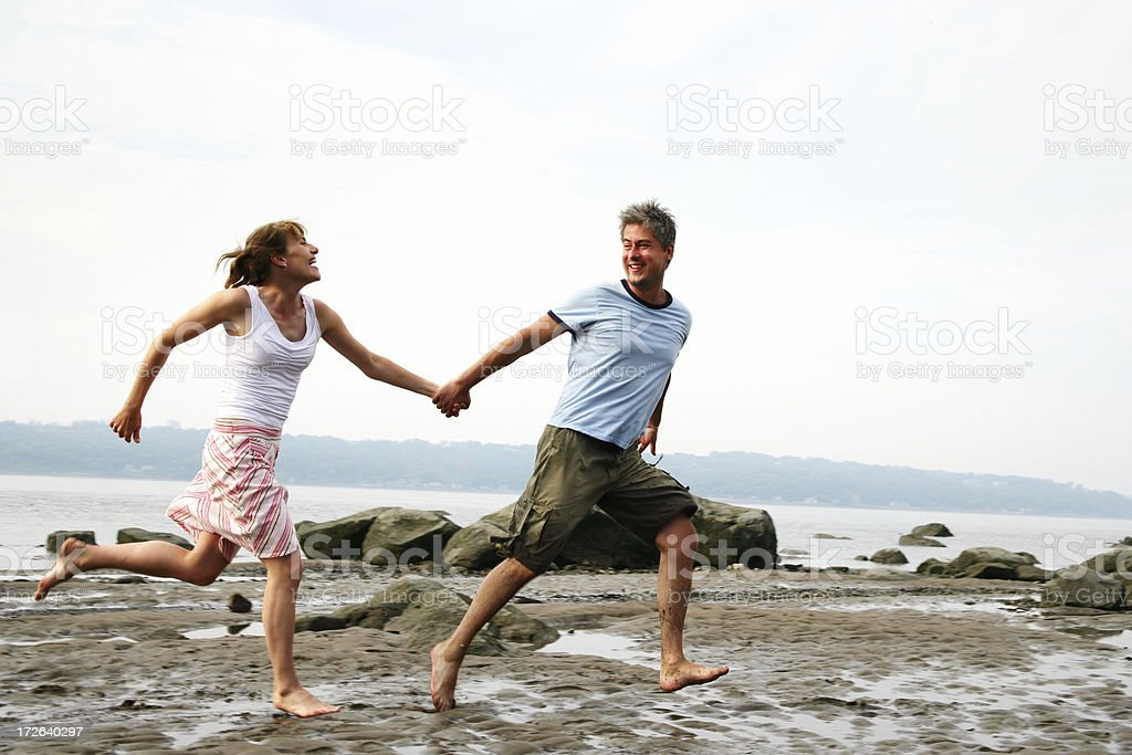 Couple running on the beach royalty-free stock photo