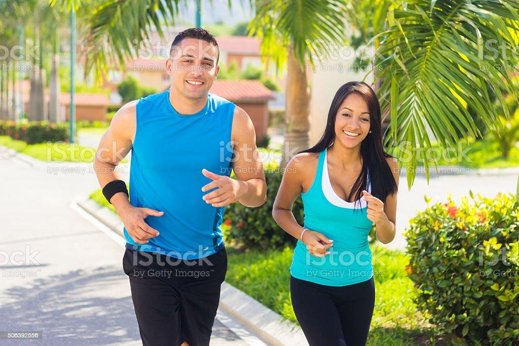 Couple running outdoors stock photo