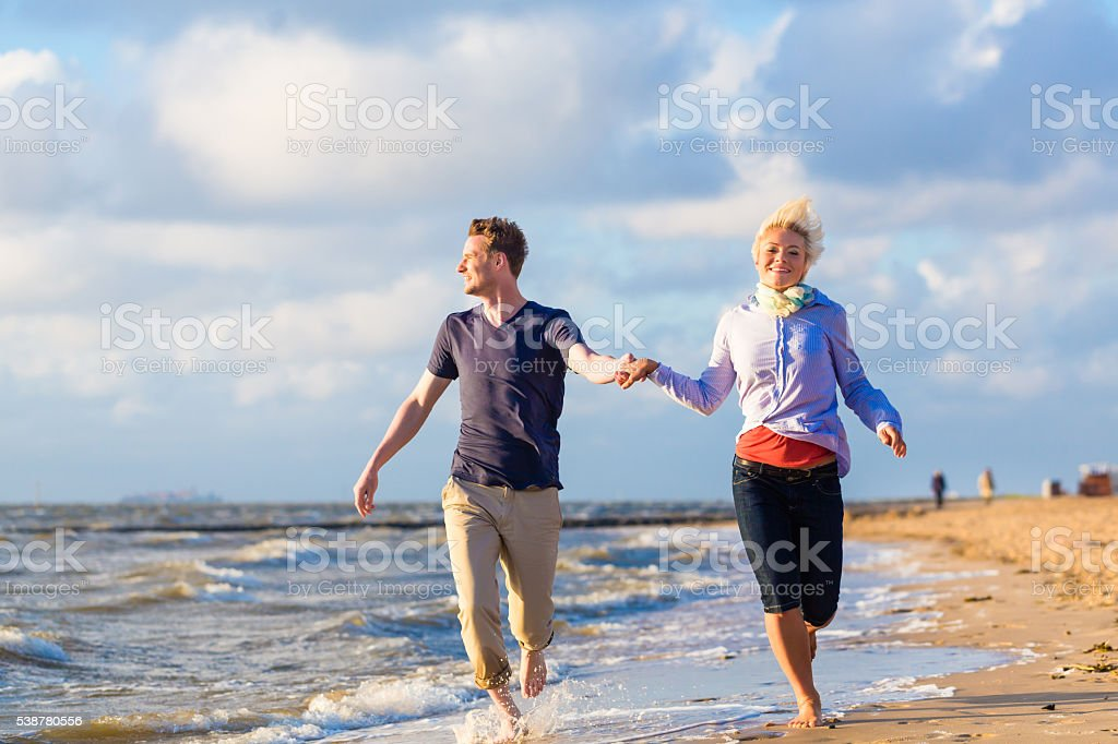 Couple running through sand and waves at beach stock photo