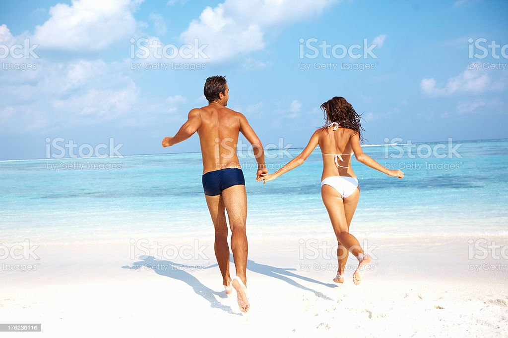 Couple running together on beach stock photo