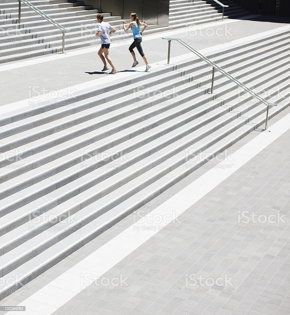 Couple running up urban staircase stock photo