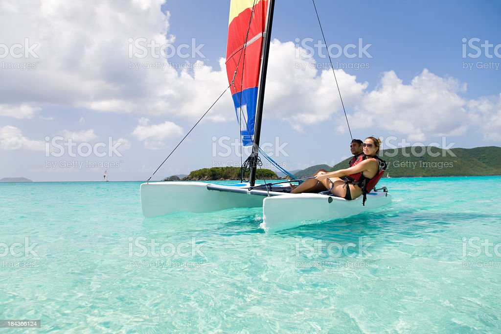 couple sailing a catamaran in the Caribbean stock photo