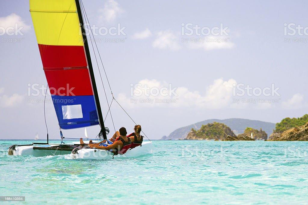 couple sailing a catamaran in the Virgin Islands stock photo