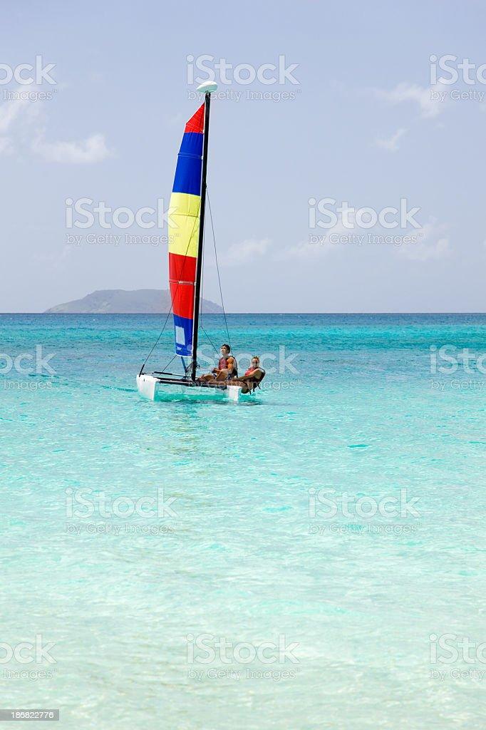 couple sailing on a catamaran in the Caribbean Sea stock photo