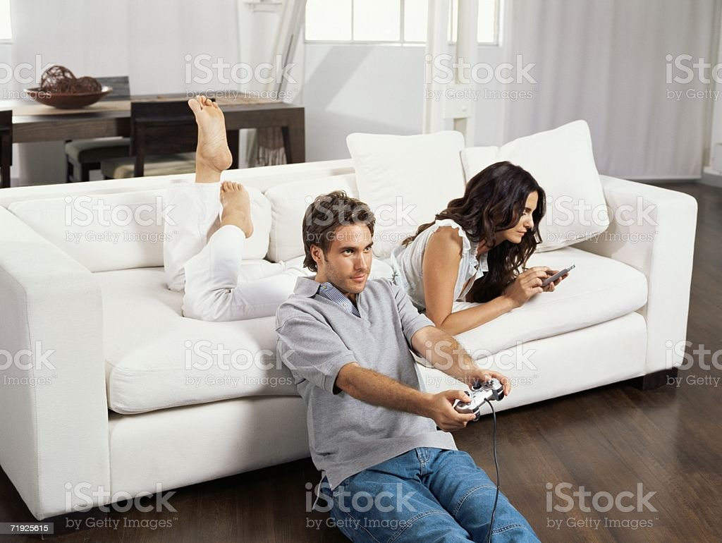 Couple sat in living room stock photo