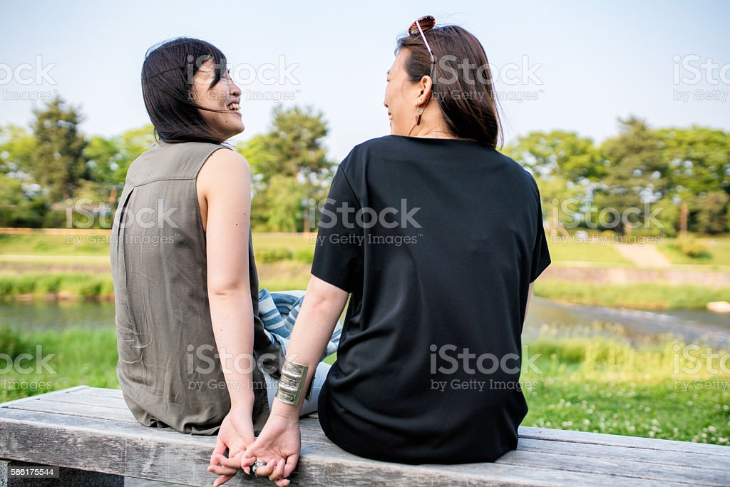 LGBT couple sat lovingly together stock photo