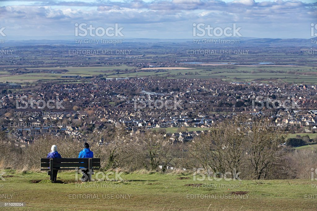 Couple sat on a bench, taking in the stunning view stock photo
