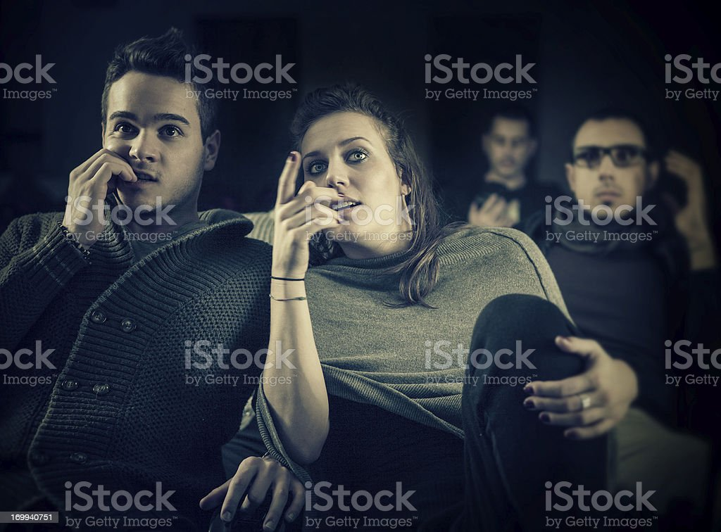 Couple scared at the cinema, watching horror movie stock photo