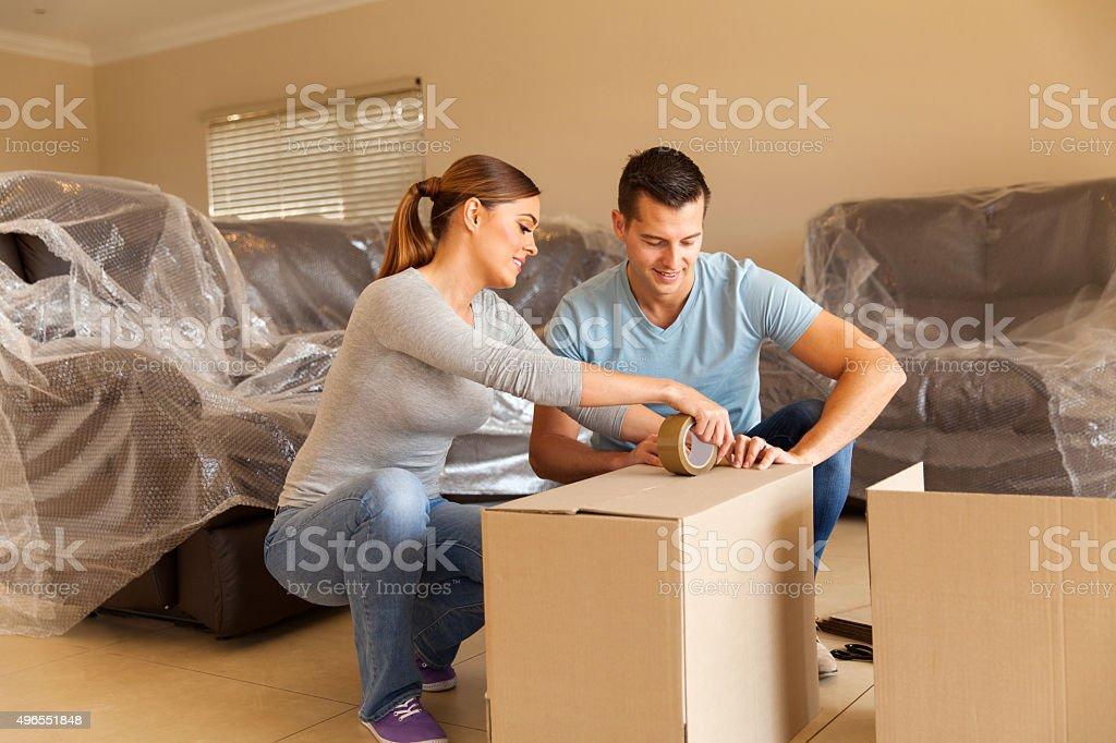 couple sealing moving boxes stock photo
