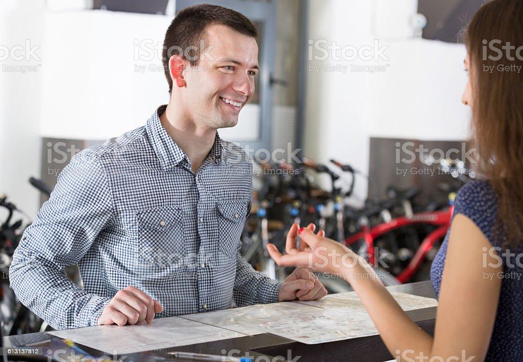 Couple selecting bikes at rental agency stock photo
