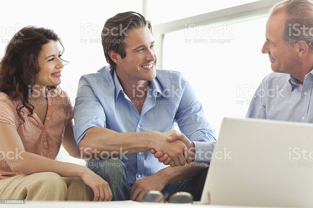 Couple shaking hands with financial advisor stock photo